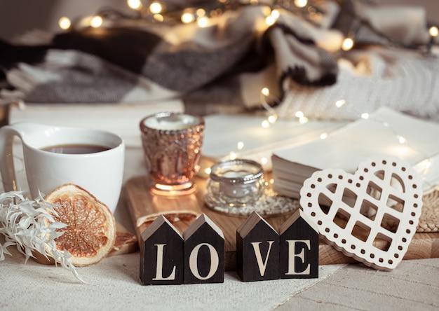 Nature morte avec le mot amour en bois, une tasse de boisson et des détails de décoration cosy avec des lumières.