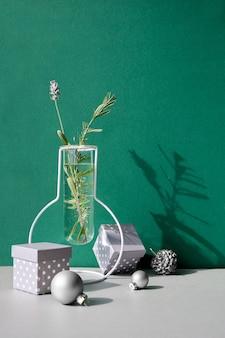 Nature morte de noël, arrangement minimal avec des fleurs d'hiver dans un vase en verre moderne et un décor de noël blanc