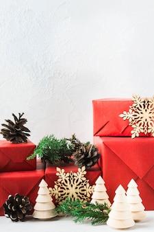 Nature morte de noël avec des cadeaux en papier rouge, jouets en bois et décoration naturelle
