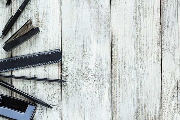 Nature morte en noir et blanc: bloc-notes vide, cahiers, stylo, crayon, lunettes, sac à main.