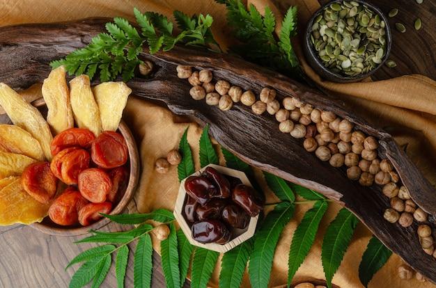 Nature morte de noix et de fruits secs sur une table en bois avec des feuilles de fougère