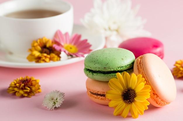 Nature morte et nourriture photo de macarons de gâteau dans une boîte cadeau avec des fleurs, une tasse de thé