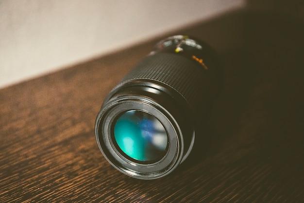 Nature morte d'un objectif de caméra sur un morceau de bois avec dégradé de couleur