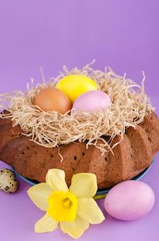 Nature morte de pâques, gâteau de pâques, œufs de poulet et de caille, sur fond violet.