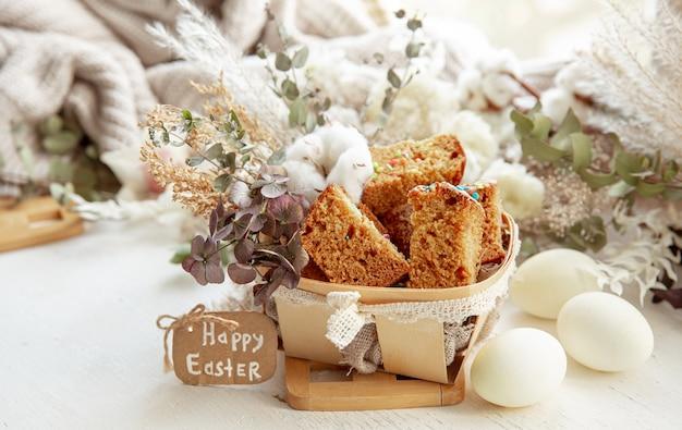 Nature morte de pâques avec des morceaux de cupcake festif, des œufs et des fleurs sur un fond clair flou. concept de vacances de pâques.