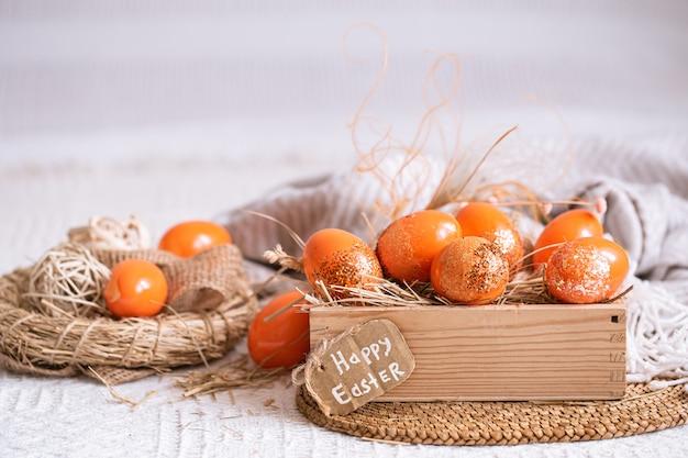Nature morte de pâques avec des oeufs orange, décor de vacances