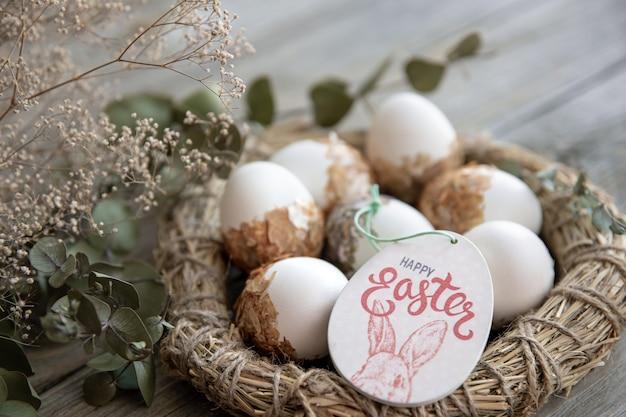 Nature morte de pâques avec des oeufs de pâques décorés et nid décoratif sur une surface en bois avec des brindilles sèches