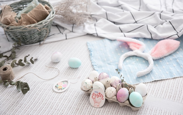 Nature morte de pâques avec des oreilles de lapin de pâques décoratives, un plateau d'oeufs de fête et des éléments décoratifs. le concept de la préparation des vacances de pâques.