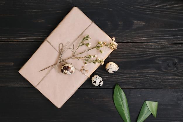 Nature morte de pâques rustique avec cadeau en papier craft, oeufs de caille, branches de saule, oreilles de lapin et décorations sur fond sombre