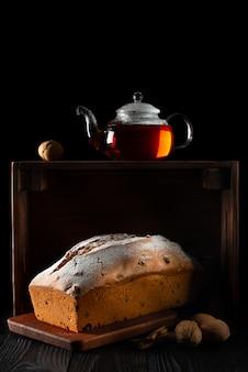 Nature morte avec un petit gâteau et du thé sur un fond sombre