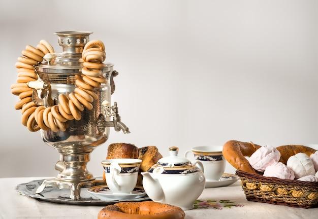 Nature morte avec petits pains, bagels, guimauves et un samovar sur la table