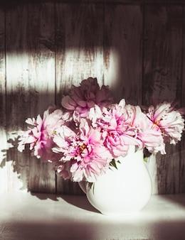 Nature morte avec des pivoines sur un mur en bois minable avec la lumière du soleil de la fenêtre
