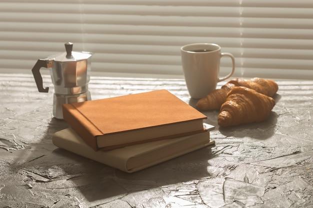Nature morte pour une agréable tasse de café du matin et des croissants avec deux livres sur la table pour le déjeuner