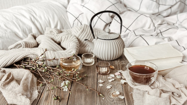 Nature morte printanière confortable avec bougies, thé, bouilloire sur une surface en bois dans un style rustique.