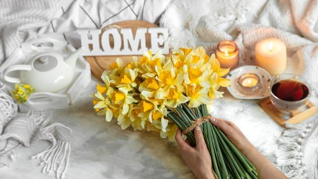 Nature morte de printemps avec une tasse de thé et de fleurs. fond clair, maison fleurie et confortable.