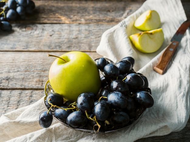 Nature morte raisins et pommes dans une assiette vintage sur fond en bois rustique