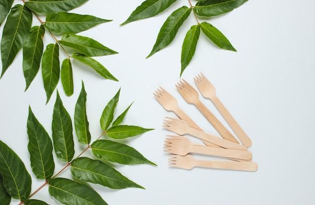 Nature morte respectueuse de l'environnement. fourchettes en bois jetables sur fond blanc avec des feuilles tropicales vertes. couverts en matériaux naturels