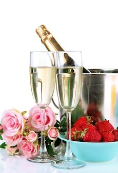 Nature morte romantique avec champagne, roses fraises et roses, sur blanc