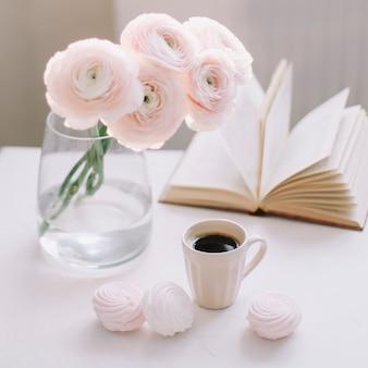 Nature morte romantique de printemps avec des fleurs, une tasse de café, un livre et des guimauves