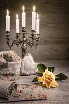 Nature morte avec rose jaune, coeur en peluche et chandelier vintage