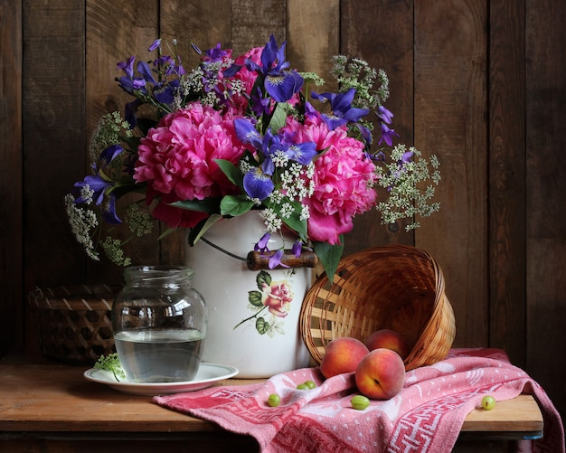 Nature morte rurale avec un bouquet de fleurs et de fruits.