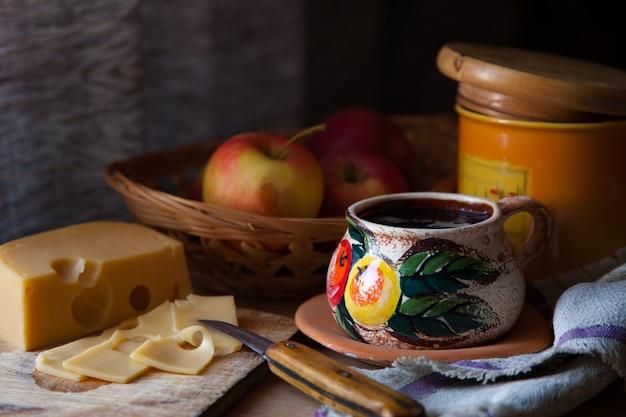 Nature morte rustique avec du fromage, des pommes et du thé.