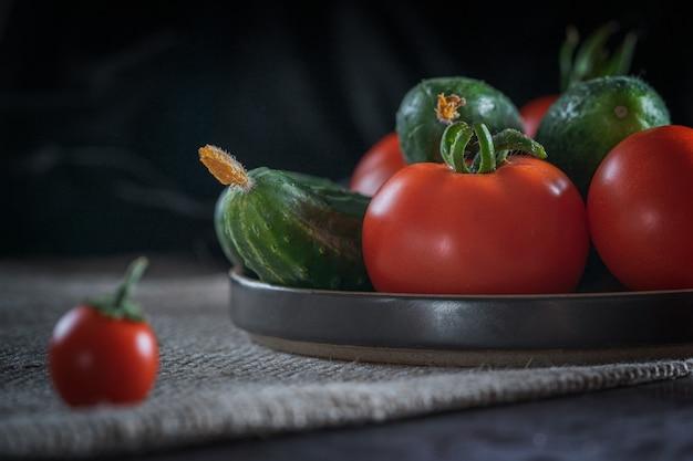 Nature morte rustique avec des légumes frais: tomates rouges, concombres verts, ail, aneth sur fond sombre.