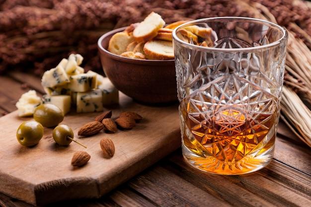 Nature morte rustique avec whisky et snacks.