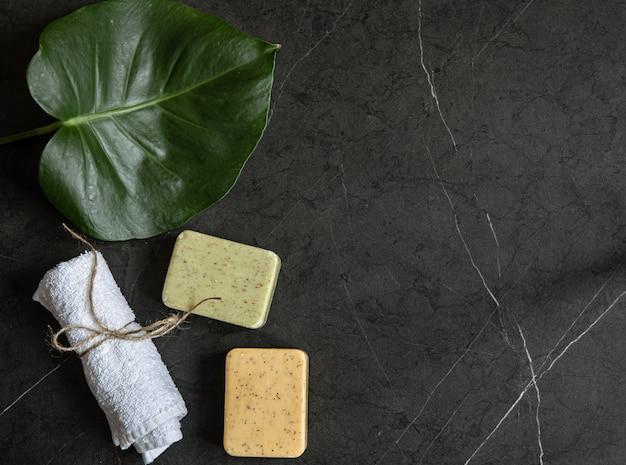 Nature morte avec une serviette et du savon sur un espace de copie de surface en marbre sombre. concept de soins du corps.