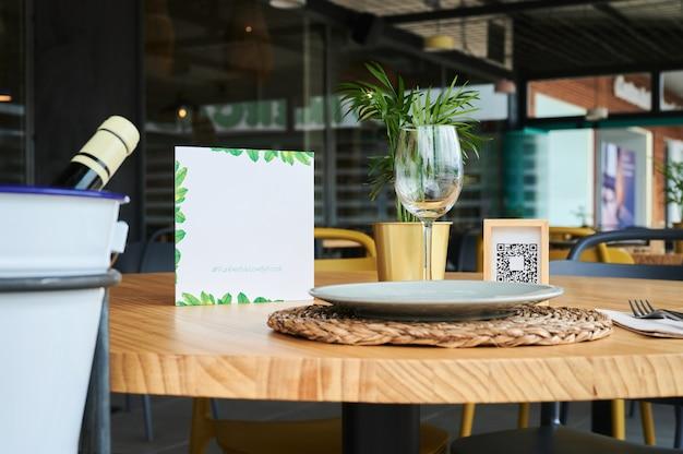 Nature morte d'une table de restaurant avec une assiette vide et un verre à vin, un panneau propre avec un faux code qr et une bouteille de vin.
