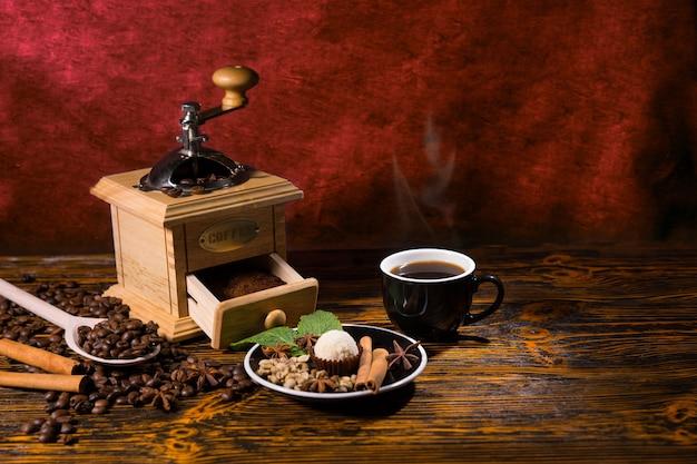 Nature morte d'une tasse de café chaud sur une table en bois rustique à côté d'un moulin à main et d'une petite assiette à la truffe et d'une variété de garnitures d'épices, entourée de grains de café torréfiés épars