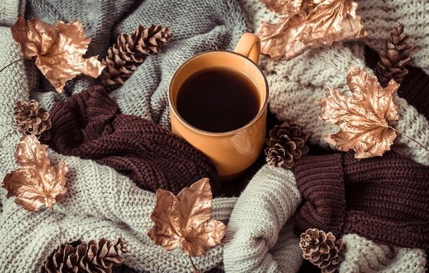 Nature morte tasse de thé avec des feuilles d'automne et un pull.