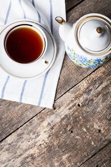 Nature morte avec tasse de thé et nappe sur table en bois