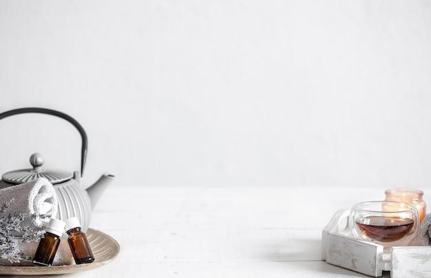Nature morte avec théière, thé, bouteilles d'huile et brins de lavande. fond de concept d'aromathérapie et de soins de santé