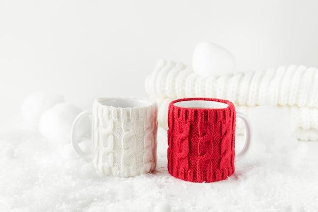Nature morte sur le thème de l'hiver avec deux tasses de thé, décor tricoté aux couleurs blanc et rouge.