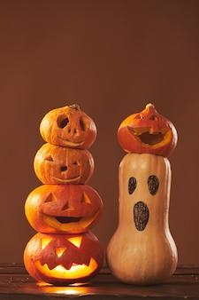 Nature morte tourné en studio de composition de citrouilles mûres sculptées et courge peint pour la décoration de fête d'halloween, surface brune