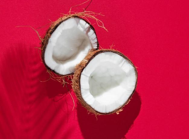 Nature morte tropicale minimaliste.deux moitiés de noix de coco hachée avec des ombres de feuilles de palmier sur fond rouge. concept de mode créatif.