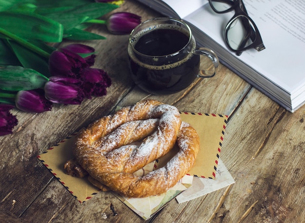 Nature morte avec des tulipes, un livre, un café et un bretzel sur le vieux fond en bois
