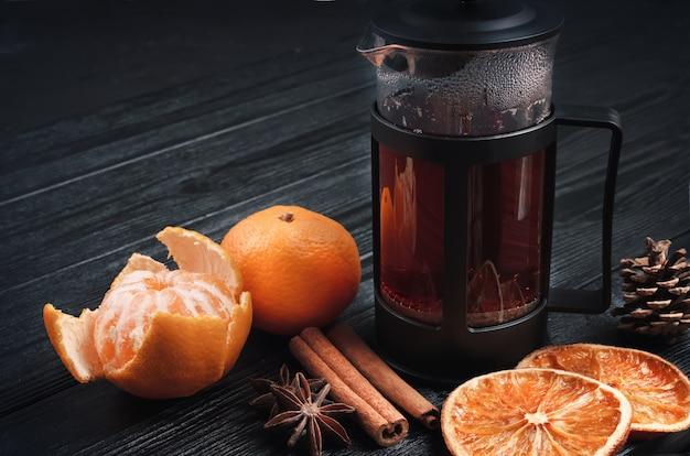 Nature morte vintage de noël d'hiver: une presse française avec du thé, des mandarines, des oranges séchées, des bâtons de cannelle et des étoiles d'anis sur une surface noire texturée