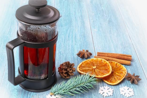 Nature morte vintage de noël d'hiver: une presse française avec du thé noir, des mandarines, des oranges séchées, des bâtons de cannelle et des étoiles d'anis sur une surface en bois bleue texturée