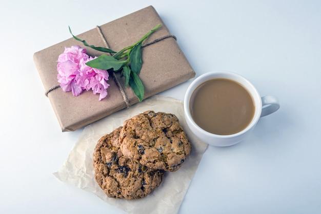 Nature morte vintage romantique avec jolie boîte-cadeau enveloppée de papier kraft brun et décorée de fleur rose sur fond blanc
