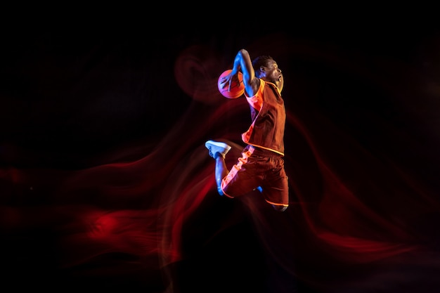 Nature mystérieuse. jeune basketteur afro-américain de l'équipe rouge en action et néons sur fond sombre de studio. concept de sport, mouvement, énergie et mode de vie dynamique et sain.