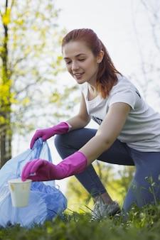 Nature propre. faible angle de belle femme bénévole transportant un sac poubelle tout en ramassant une tasse en papier