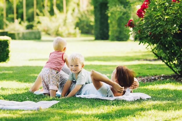 Nature verte familiale mère avec enfants dans le parc d'été jeune femme se relaxant avec ses enfants