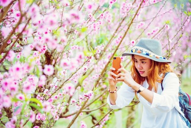 Nature de voyage asiatique femme. voyage relax. photographié dans un jardin de fleurs.