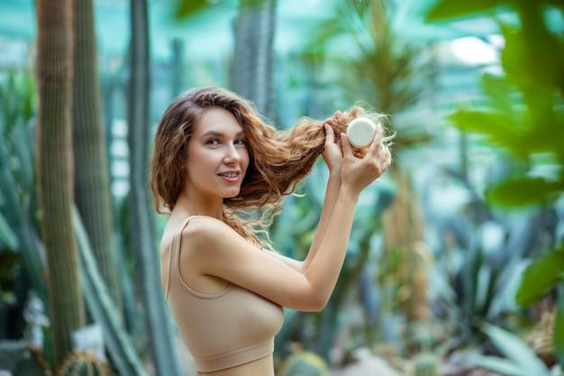 Naturel. jolie femme aux cheveux longs avec une barre de savon dans une maison grise