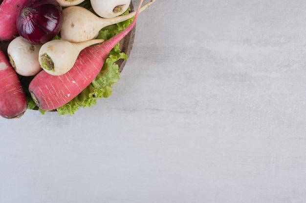 Navets blancs et rouges avec oignon sur morceau de bois. photo de haute qualité