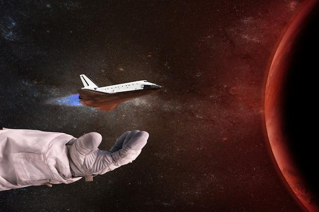 La navette entre les mains de l'astronaute face à la planète rouge