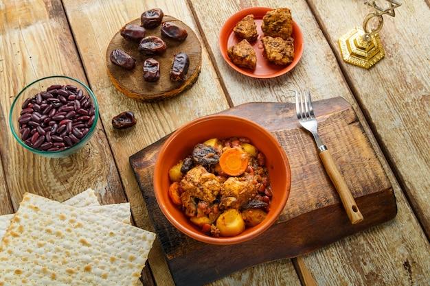 Navette de plat juif avec de la viande dans un plat en argile sur une table en bois près du matzo et des ingrédients.