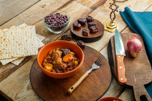 Navette de plat juif avec de la viande dans un plat sur une table en bois à côté du pain azyme. fourchette et ingrédients.